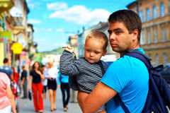 Father with baby walking through crowded city street Royalty Free Stock Image