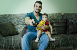 Father and baby watching tv. Father holds baby with pacifier and watching tv with remote control Stock Image
