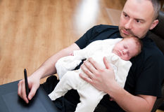 Father and baby while working. Father holding his baby girl daughter on his chest while working on computer at home Stock Photos