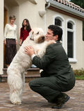 Father is back from work. Dog greeting businessman Royalty Free Stock Photos