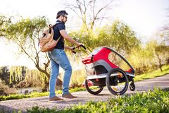 A father with jogging stroller on a walk outside in spring nature. A father with backpack and jogging stroller on a walk outside in spring nature Stock Photos