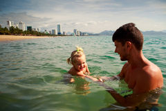 Father backside teaches daughter to swim in shallow sea water Stock Photo