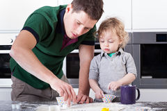 Father baking cookies with son Royalty Free Stock Photography