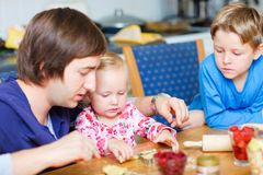 Father baking with his two kids Stock Image