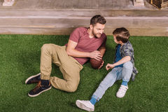 Father with ball and little son laying on the grass at backyard. Dad and son playing Royalty Free Stock Image