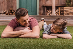 Father with ball and little son laying on the grass at backyard Stock Photo