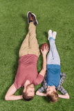 Father with ball and little son laying on the grass at backyard. Dad and son playing Royalty Free Stock Photography
