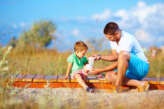 Father bandaging injured leg of kid Stock Photo