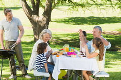 Father at barbecue grill with family having lunch in park Royalty Free Stock Photo