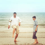Father on the beach kicking the ball with his son Stock Photos