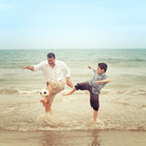 Father on beach kicking the ball while his son tries to get it Royalty Free Stock Photo