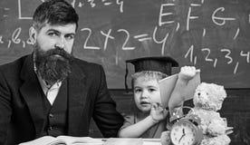 Father with beard, teacher teaches son, kid boy. Teaching kid concept. Teacher and pupil in mortarboard, chalkboard on stock photos