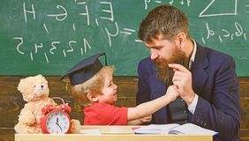Father with beard, teacher teaches son, little boy, while child beating him. Kid cheerful boxing, beating dad. Playful. Child concept. Teacher and pupil in stock photography