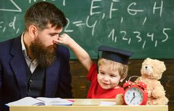Father with beard, teacher teaches son, little boy, while child pinching his nose. Kid cheerful play with dad. Playful. Child concept. Teacher and pupil in royalty free stock photos