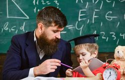 Father with beard, teacher teaches son, little boy. Individual schooling concept. Kid studies individually with teacher. At home. Teacher and pupil in royalty free stock photo