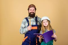 Father bearded man and daughter hard hat helmet uniform renovating home. Home improvement activity. Kid girl planning. Father bearded men and daughter hard hat stock image