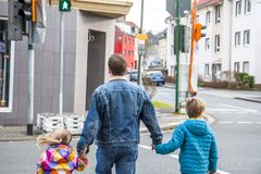 Father being an everyday superhero guiding and helping son and daughter.  Stock Image