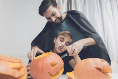 A man helps a boy dressed as a monster to cut a scary pumpkin for Halloween Royalty Free Stock Images