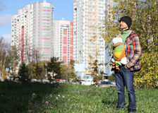 Father in a black knitted hat with infant baby in sling, full gr. Owth, on the background of the urban landscape, autumn Royalty Free Stock Photos