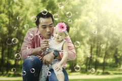 Father blowing bubble soap with his daughter Royalty Free Stock Images