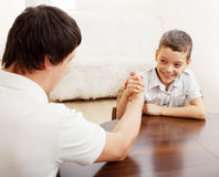 Father and boy arm wrestling. Father and son arm wrestling. Dad play with child Stock Image