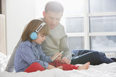 Father with boy listening music on headphones in bedroom Royalty Free Stock Image