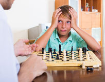 Father and boy playing chess. At home, boy losing royalty free stock images