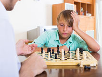 Father and boy playing chess Stock Images