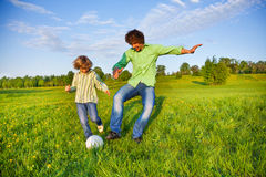Father and boy playing football together in park Stock Photo