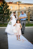 Father and bride are going to the altar and girl is throwing rose petals Royalty Free Stock Images