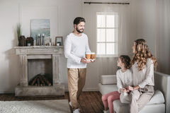 Father bringing coffee in paper cups for mother and daughter at home Royalty Free Stock Photo