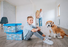 Father brings the cardboard box in New home. Little son with dog sit on the floor Royalty Free Stock Photos