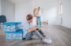 Father brings the cardboard box in New home. Little son sist on the floor Royalty Free Stock Photos