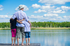The father brought the children on nature. Children and dad came to rest on the river Stock Photos