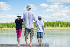 Father brought his daughter and son to the pier to look at the beautiful lake royalty free stock photos