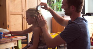 Father Brushes Daughter's Hair As She Sits At Table. Girl sits at table as father brushes her hair.Shot on Sony FS700 at frame rate of 25fps stock video