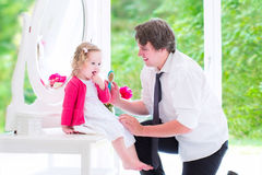 Father brushing his daughter hair Stock Image