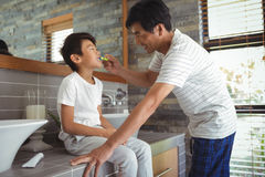 Father brushing his sons teeth in bathroom. At home stock photography