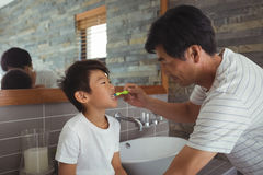 Father brushing his sons teeth in bathroom. At home Royalty Free Stock Photos