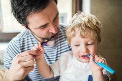 Father brushing his teeth with a toddler boy at home. Paternity leave Stock Photography