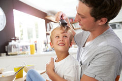 Father Brushing Son's Hair At Breakfast Table Stock Photos