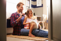 Father brushing young daughter's hair Royalty Free Stock Photos