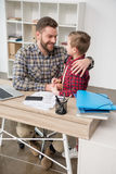 Father businessman hugs his son. At home office royalty free stock images