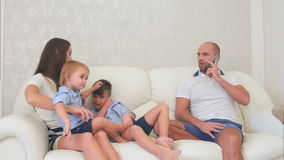 Father busy talking on the phone while little boys playing with their mother on the sofa stock video footage