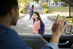 Father In Car Dropping Off Daughter In Front Of School Gates stock photos