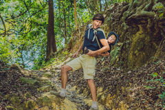 The father carries his son in a baby carrying is hiking in the f. Orest. Tourist is carrying a child on his back in the nature of Vietnam Stock Photos