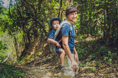 The father carries his son in a baby carrying is hiking in the f stock photo