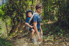 The father carries his son in a baby carrying is hiking in the forest. Tourist is carrying a child on his back in the nature of Vi Stock Photography