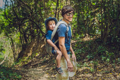 The father carries his son in a baby carrying is hiking in the forest. Tourist is carrying a child on his back in the nature of Vi Stock Images