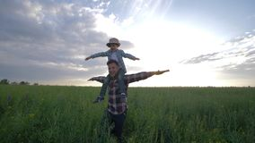 Father carries his son on shoulders walking through rapeseed field on background sky in slow motion, family game in open. Father carries his son on shoulders stock video footage